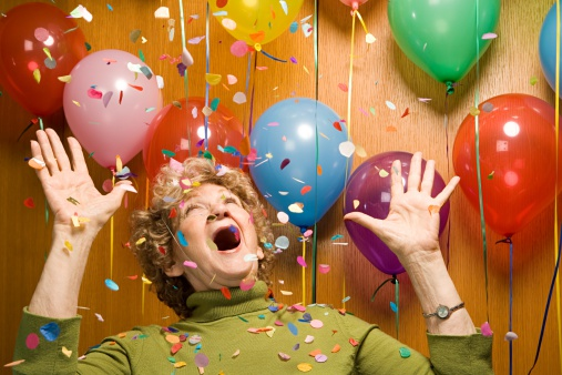 woman being surprised surrounded by colourful balloons and confetti