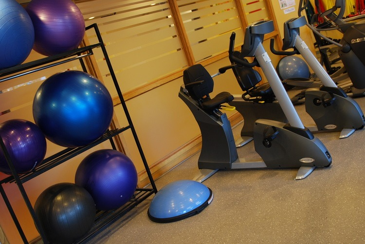 exercise balls on shelves beside cycles