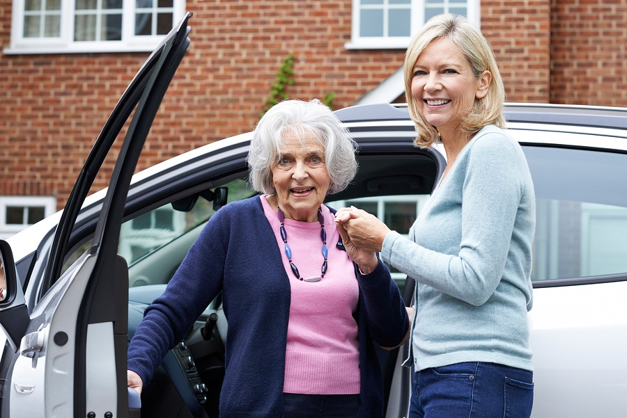 younger woman helping older woman out of vehicle