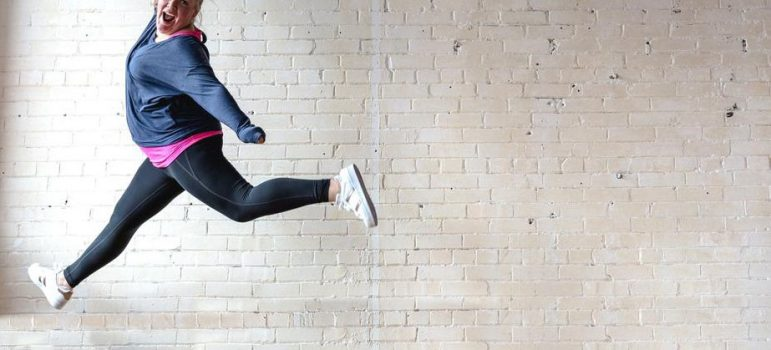 lady dressed in fitness clothes jumping