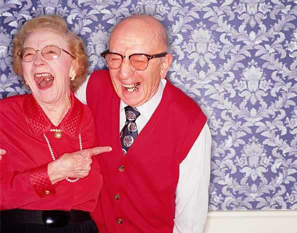 elderly couple laughing, dressed in red