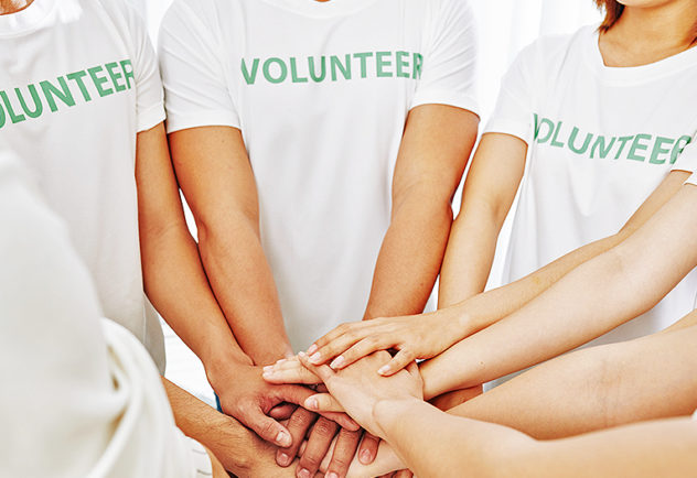 group of volunteers with hands stacked