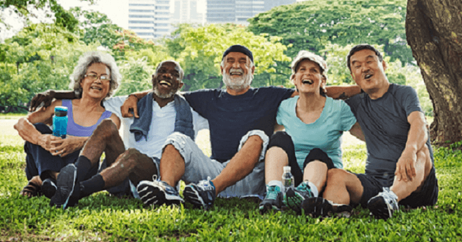 group of happy fit seniors sitting on the grass