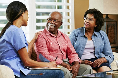 care worker sitting on couch with older couple
