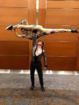 man holding woman in acrobatic pose above head with one arm