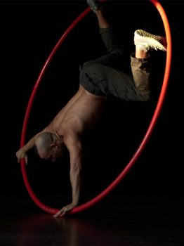 man rolling circles in a large hoop