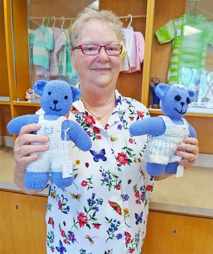 older lady volunteer holding two baby toy bears
